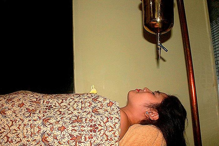 頭・肩・腕のマッサージ後、温オイルを額の「第3の目」に垂らしていきます。
