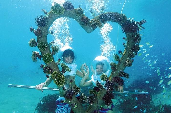 海の中でハート型サンゴのオブジェと一緒に記念撮影する、シーウォーカーLOVEコーラルプラン